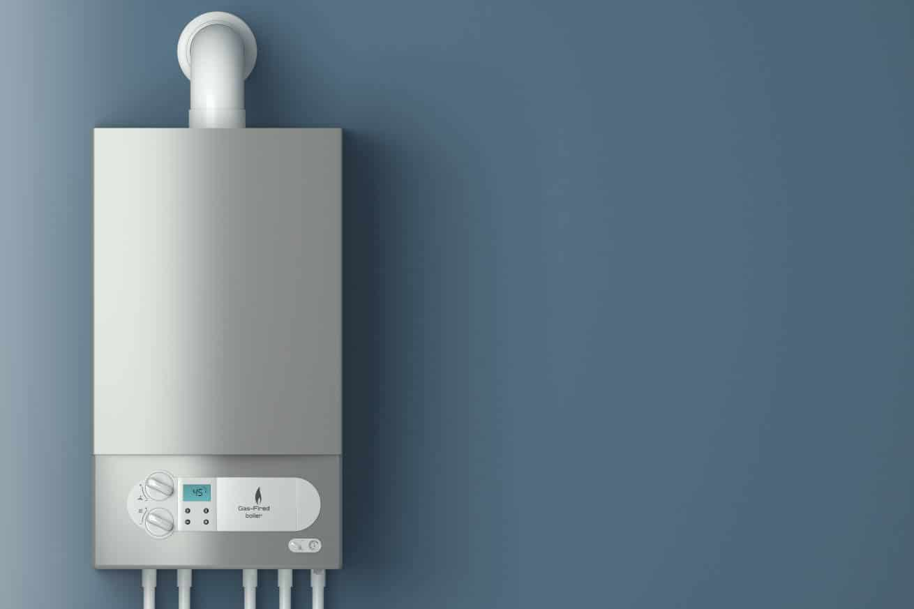 A tankless water heater hanging on a gray wall.