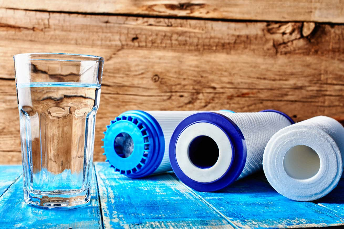Clear glass of water next to carbon filters